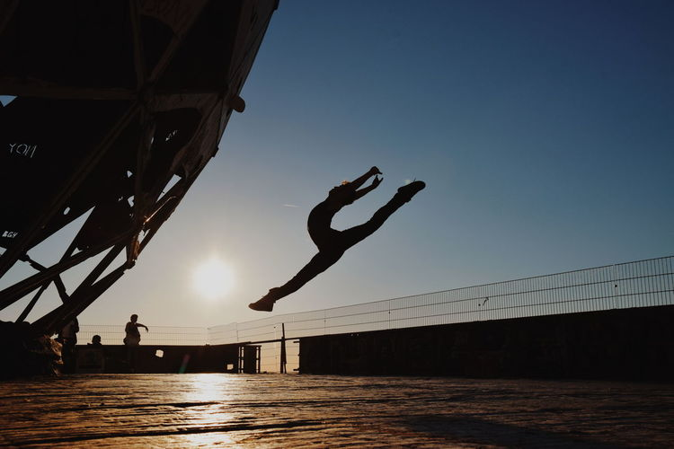 Silhouette Ballet Dancer Dancing Against Sky During Sunset