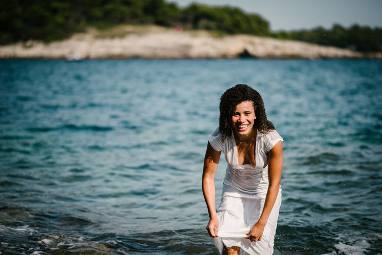 Portrait of smiling young woman in sea