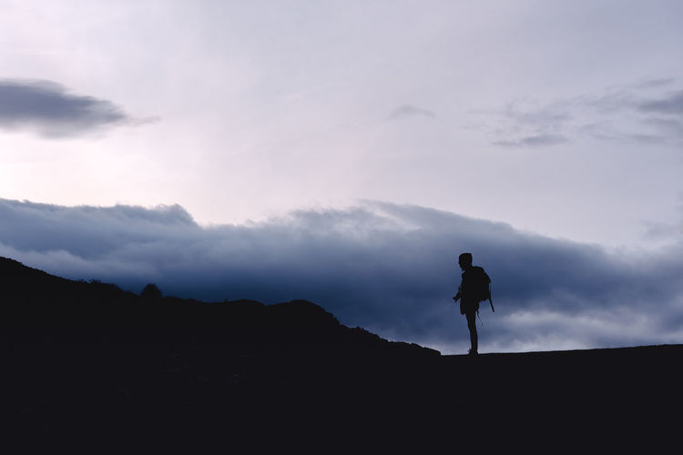 Silhouette man standing on mountain against sky
