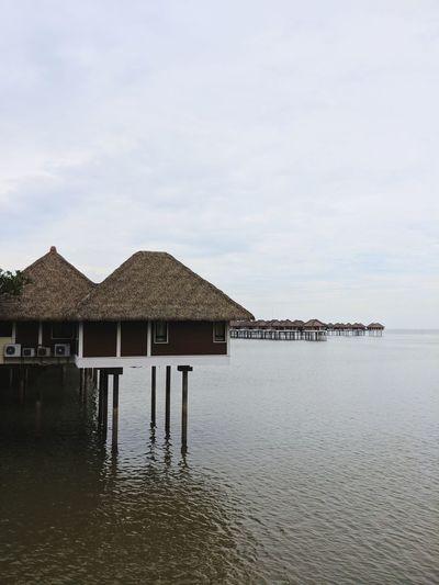 Stilt house by sea against sky