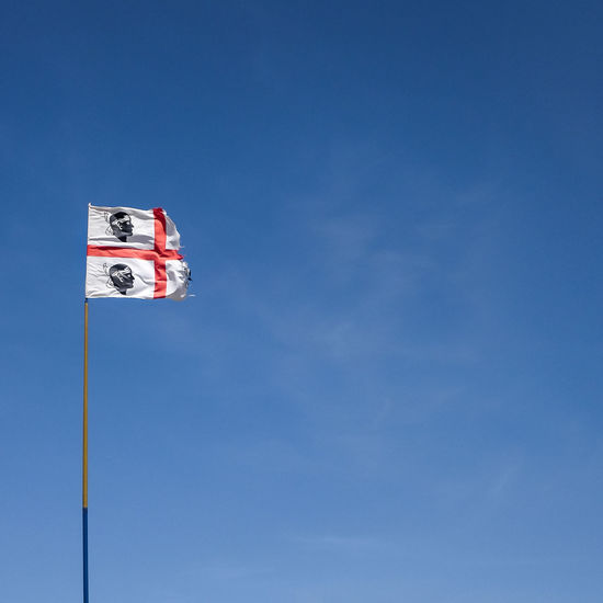 a worn out sardinian flag waving in the sky Wind Power Broken Countryside Flag Sardinia Sardinian Sea Seaside Sky Torn Wind Worn Wornout