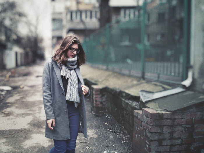 Young woman standing on footpath against building