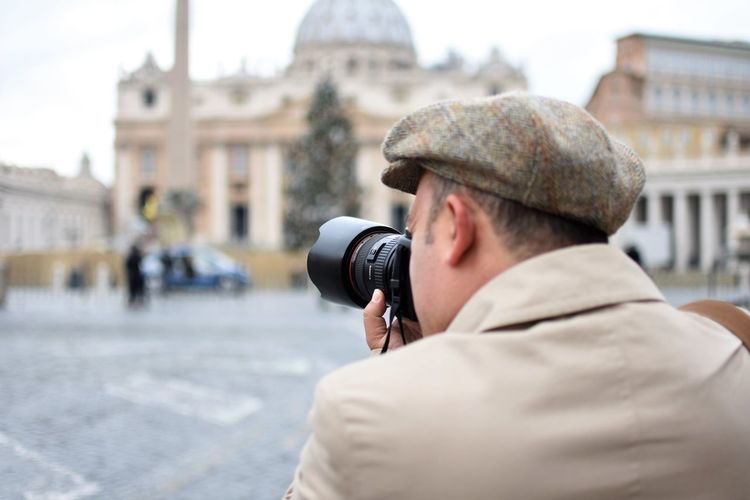 Close-up of man photographing through camera in city