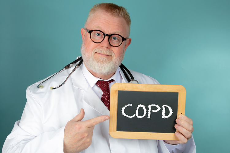 Portrait of male doctor holding slate with alphabets against green background