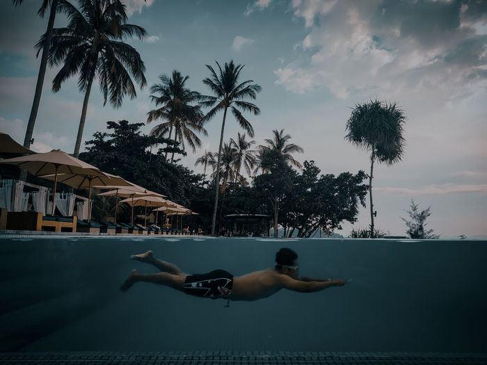 Side view of shirtless man swimming in pool against sky