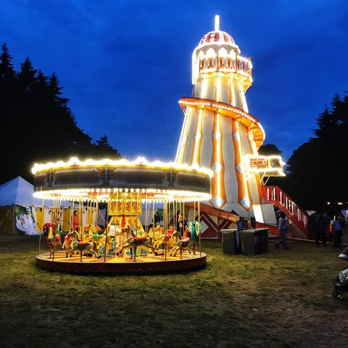 Fairground at night Fairground Lights Blue Sky Blue Night Outdoors Sky Amusement Park Leisure Activity Illuminated Real People Built Structure Carousel Amusement Park Ride Grass Tree