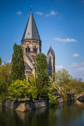 A postcard-like photo of the Church Temple Neuf on an island in the Moselle river in Metz, France Architecture Bell Tower Blue Sky Building Exterior Built Structure Church Clouds Day France Metz Moselle River No People Outdoors Place Of Worship Religion River Sky Spirituality Summer Temple Neuf Travel Destinations Tree Water