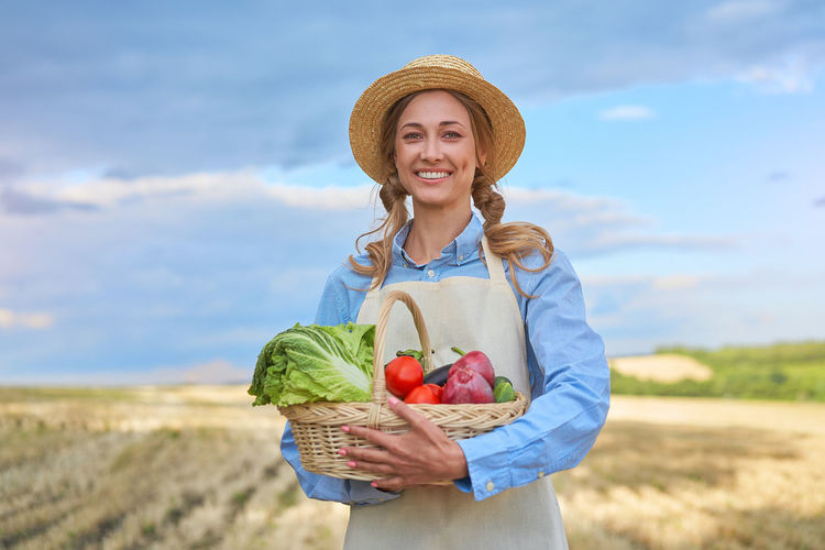 Young woman wearing hat standing at farm against sky