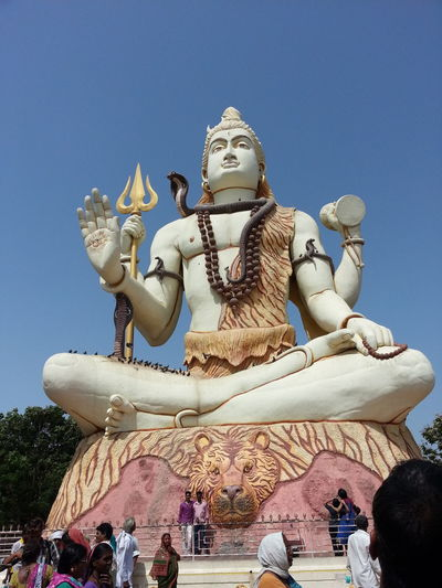 Low angle view of people visiting shiva statue against clear blue sky