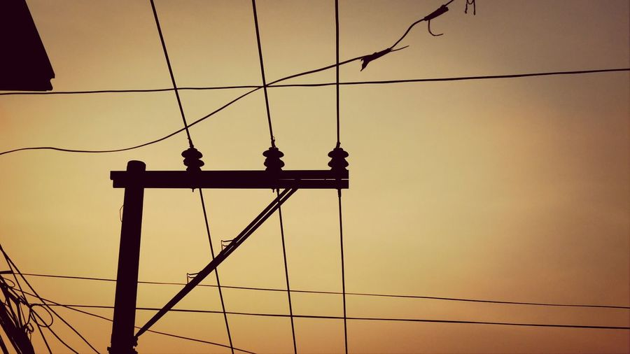 Low angle view of silhouette suspension bridge against sky during sunset
