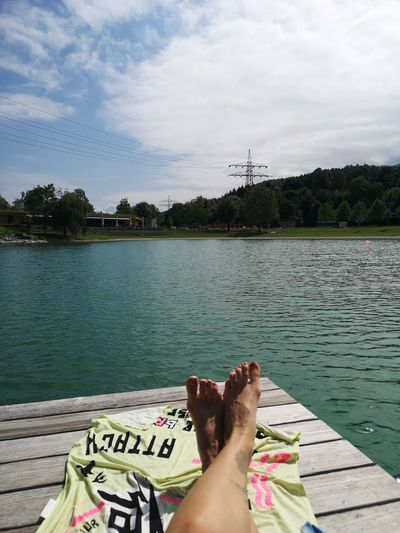 Low section of person relaxing by lake against sky