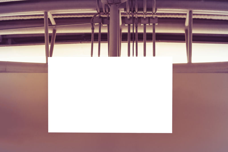 Close-up of empty paper hanging on table against white wall