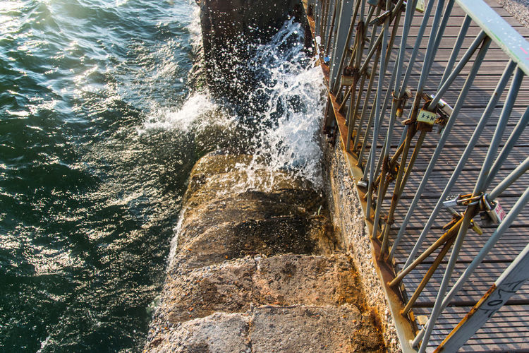 a crashing sea wave in stairs near barriers in a greek town thessaloniki Action Aquatic Sport Barrier Beauty In Nature Blurred Motion Breaking Chrasing Wave Day Flowing Flowing Water Greece High Angle View Motion Nature Nautical Vessel No People Outdoors Sea Speed Splashing Sport Staircase Transportation Water Wave