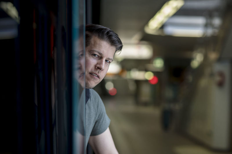 Portrait Of Young Man Entering In Train At Railroad Station