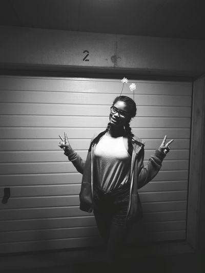 Portrait Of Happy Woman Showing Peace Signs At Night