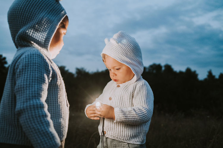 Baby boy holding illuminated light while standing with brother on field