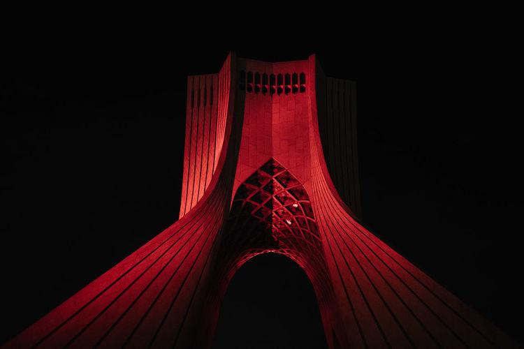 Low angle view of illuminated bridge against black background