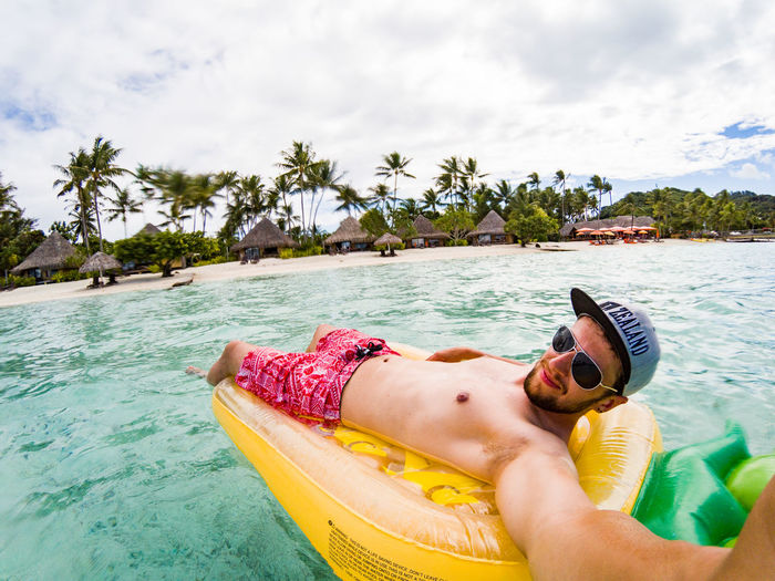 young man lying on a inflatable pineapple in the lagoon of bora bora Bora Bora  French Polynesia Pacific Travel Cloud - Sky Day Holiday Inflatable  Lagoon Leisure Activity Lifestyles Nautical Vessel One Person Palm Tree Plant Real People Sea Sky Tahiti Travel Destinations Tree Trip Tropical Climate Water Young Man The Traveler - 2018 EyeEm Awards Summer Sports