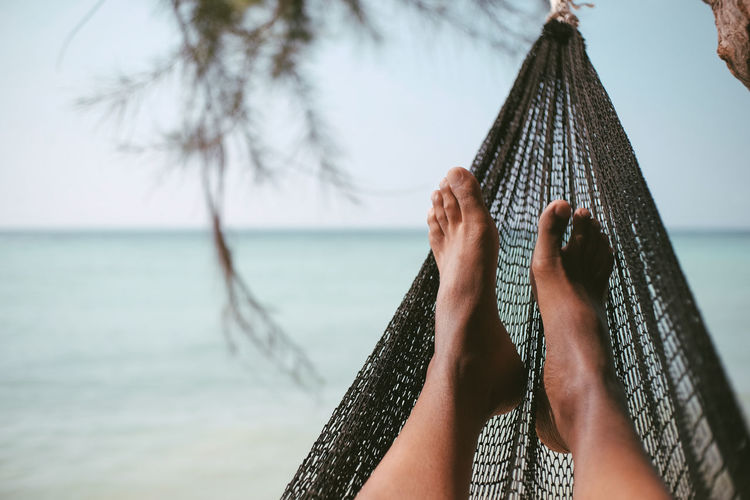 Low section of woman on hammock at beach against sky