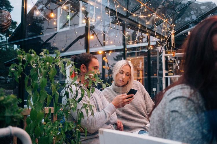 Woman using mobile phone at camera