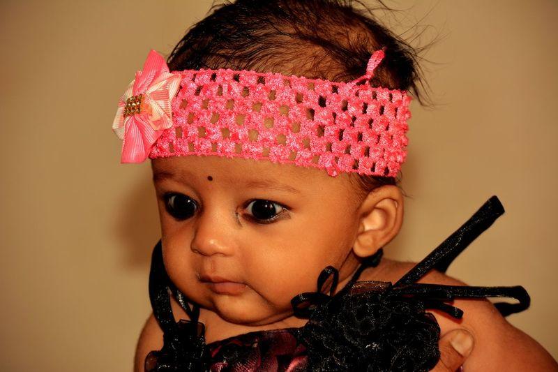 Close-Up Of Cute Girl Wearing Pink Headband At Home