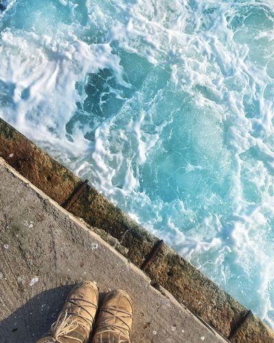 Low Section Of Person Standing On Retaining Wall Against Sea