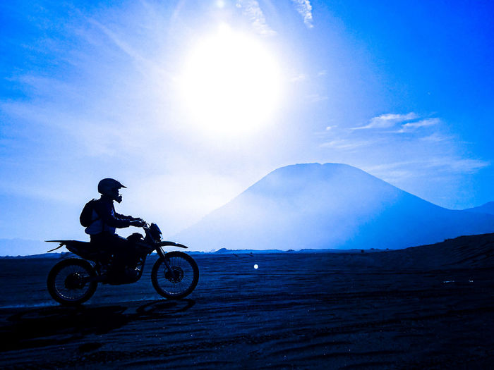Side view of man riding motorcycle on land against sky during sunset