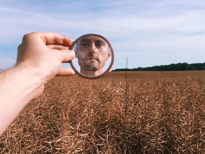 Close-Up Of Man's Reflection In Mirror Against Wheat Field