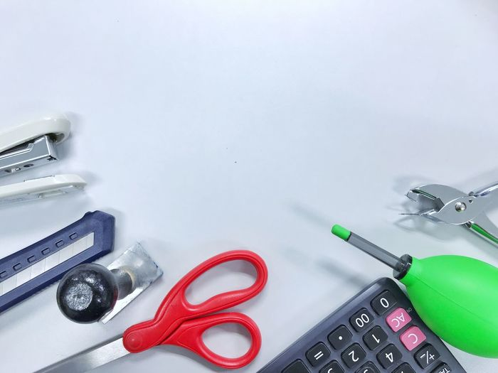 Directly above shot of office supplies on blue background