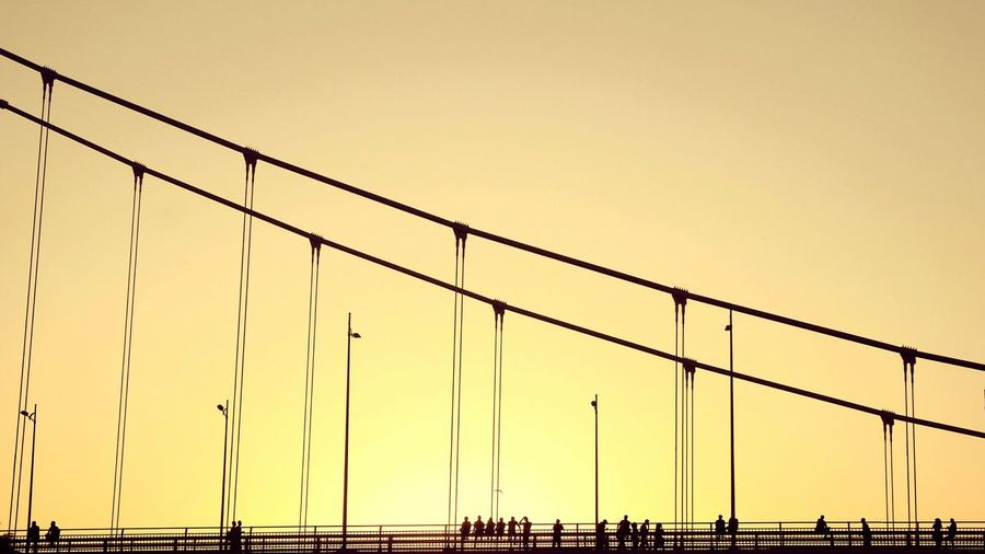 Low angle view of silhouette people on bridge against clear orange sky