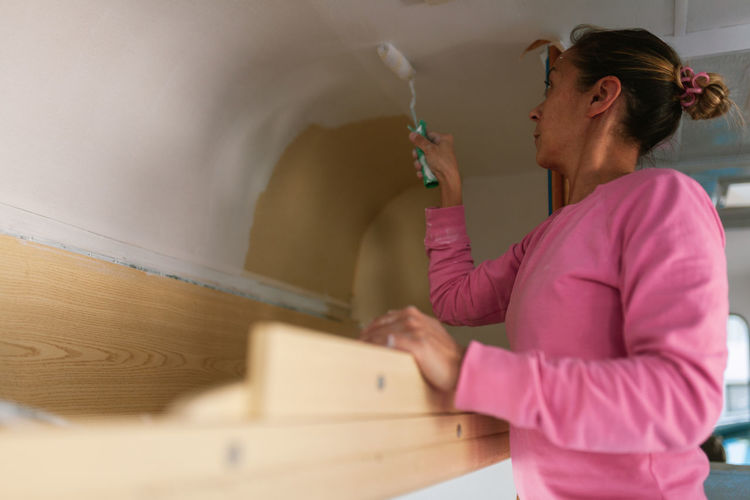 Woman painting in camper trailer