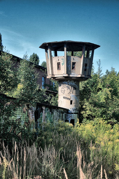 old east german Watchtower in Berlin Berlin Communism East GDR German Democratic Republic Jail Time Goes By Architecture Building Clear Sky Dilapidated East Germany East Berlin Germany Grass Jailhouse Landscape Nature No People Outdoors Prison Sky Sociallism Tower Watchtower