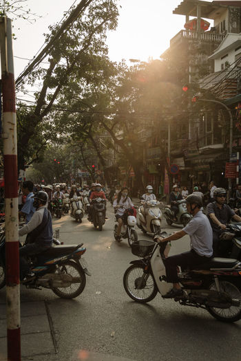 Sun set in Ha Noi, Vietnam Architecture Building Exterior Built Structure City Day Helmet Large Group Of People Men Outdoors People Scooter Street Street Art Street Life Street Light Street Photography Streetlightstudio Streetphotography Sun Sunlight Sunlight And Shadow Sunset Tree Vietnam Woman