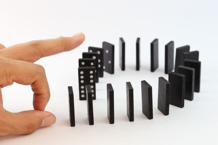 Male hand stopping (dominoes) blocks falling over Close-up Day Dominoe Pieces Dominoes Dominoes Game Finger Holding Human Body Part Human Finger Human Hand Indoors  One Person People Studio Shot White Background