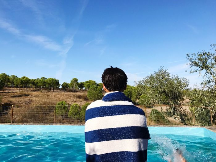Rear View Of Teenage Boy Standing At Swimming Pool