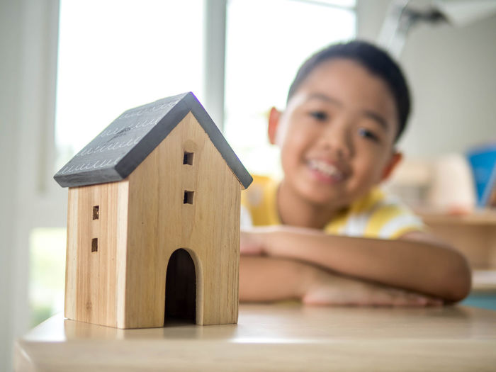 Portrait Of Smiling Boy With Model Home On Table Sitting Against Window