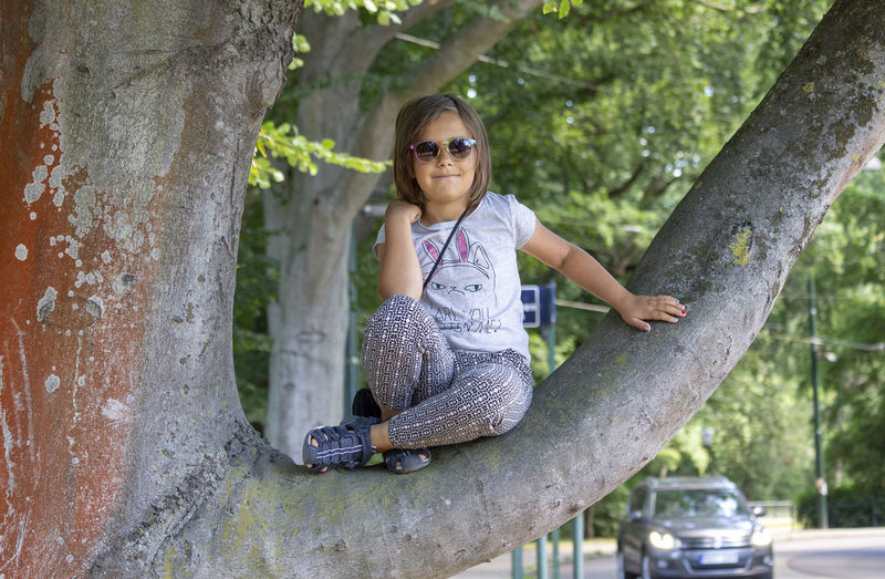 Girl with sunglasses sitting in a tree Casual Clothing Child Childhood Girl Innocence Looking At Camera One Person Outdoors Portrait Sunglasses Tree Tree Trunk