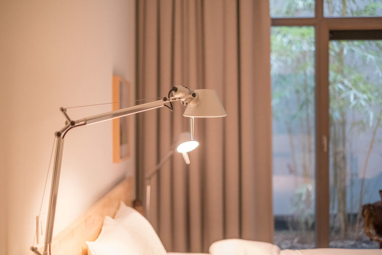 Close-up of electric lamp on bed by window at home