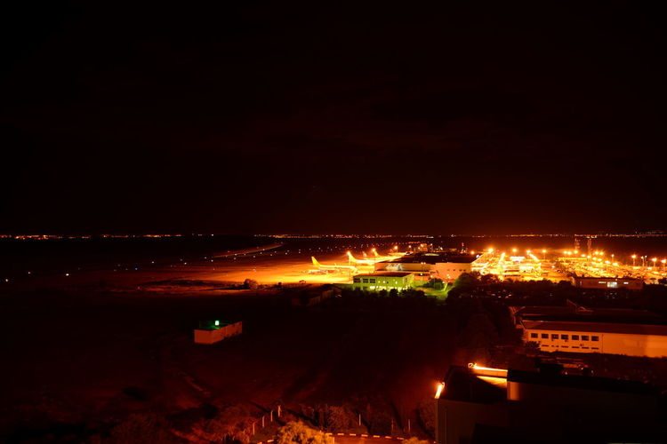 Aerodrome Runway Architecture Aviation Building Building Exterior Built Structure Burning City Cityscape Copy Space Environment Glowing Heat - Temperature High Angle View Illuminated Nature Night No People Orange Color Outdoors Residential District Sky