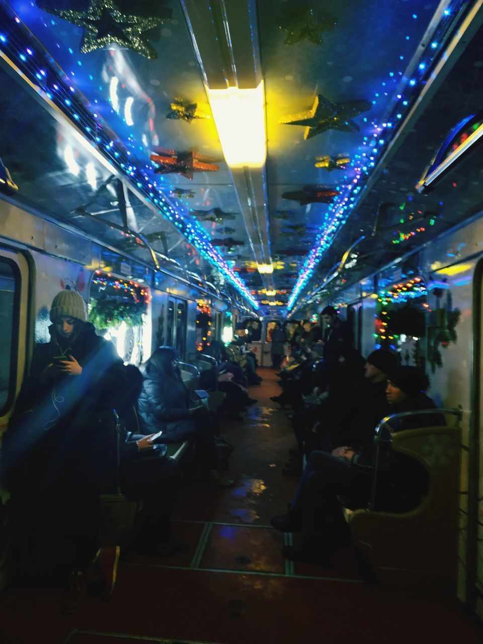 illuminated, night, lighting equipment, group of people, real people, men, architecture, city, transportation, lifestyles, motion, mode of transportation, public transportation, women, crowd, people, leisure activity, city life, adult, outdoors, light, nightlife