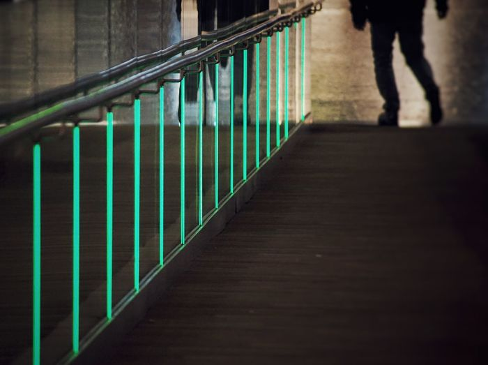 Low section of person walking by railing
