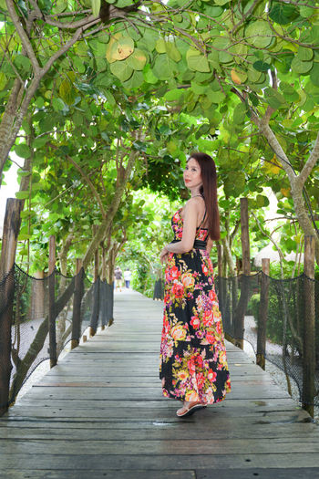 Woman standing on footpath amidst plants