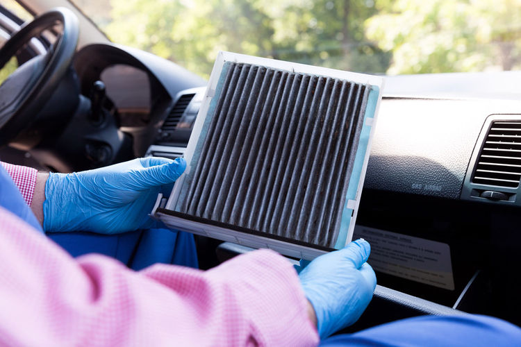 An automechanic sitting in a car, replacing an old car cabin air filter Automobile Car Parts Changing Mechanic Repairing Spare Part Air Filter Air Filter Car Airflow Allergen Automechanic Cabin Car Air Filter Car Interior Car Service Close-up Dust Maintenance Occupation Pollen Filter Protective Glove Replacement Vehicle Interior Ventilation Working