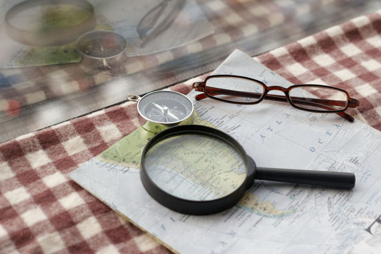 Travel concept Reflection Mirror Reflection Magnifying Glass Map Travel Vacations Holiday Exploring Eyeglasses  Eyesight High Angle View Still Life Close-up Topography Navigational Compass Sunglasses Checked Pattern