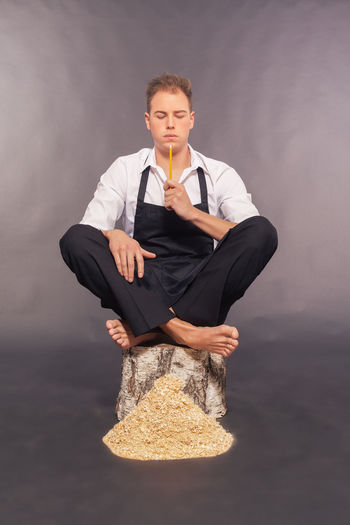 Man with pencil sitting on wood against gray background