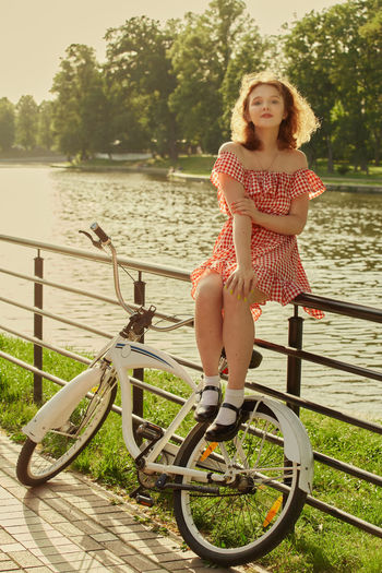 Full length of woman on bicycle by plants