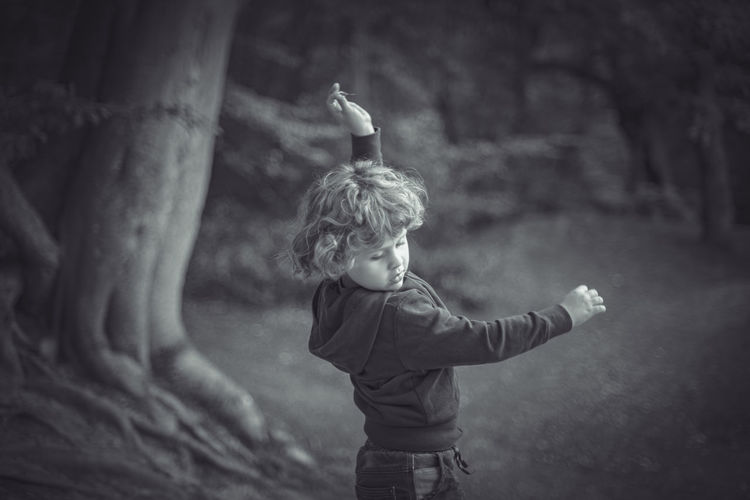 Boy dancing in the woods