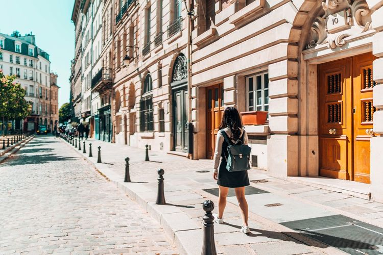 Woman walking on sidewalk by buildings