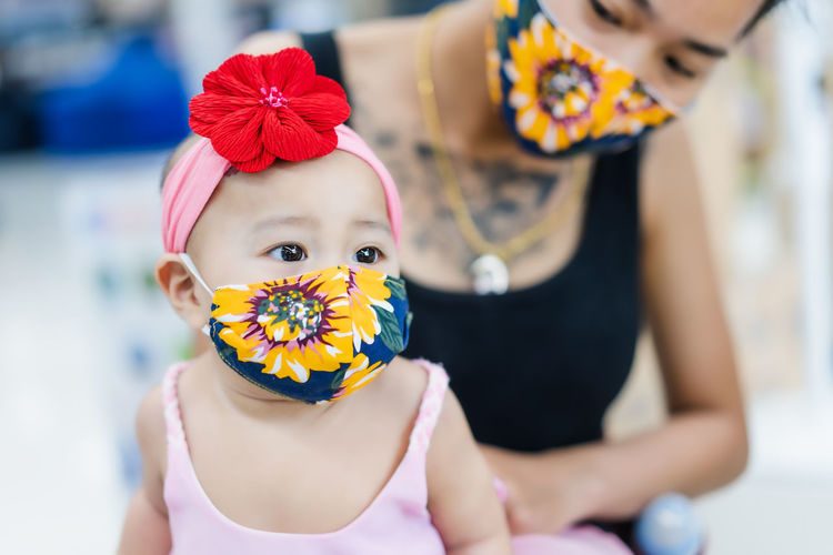 Midsection of mother with cute daughter wearing floral masks