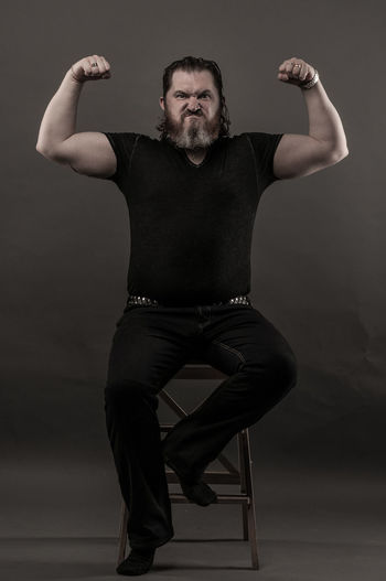 Mid Adult Man Flexing Muscles While Sitting Against Black Background